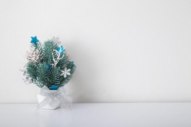 Kerstmissamenstelling met dennentakken en decoraties in wit binnenland
