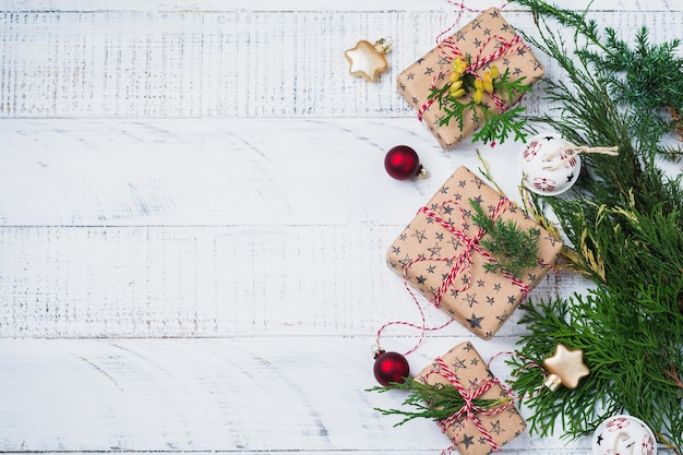Kerstmissamenstelling met dennentakken, giftdoos en snuisterijen op houten lijst. bovenaanzicht met kopie ruimte.