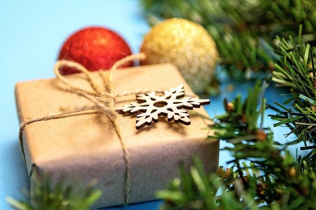 Kerstmissamenstelling met dennentakken, gouden en rode ballons, houten speelgoed op een blauw oppervlak.