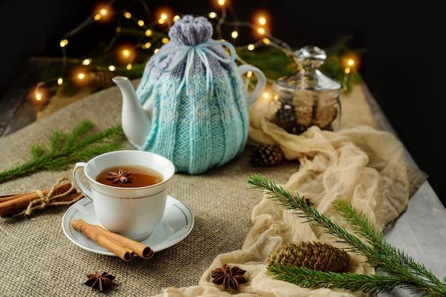 Kerstmissamenstelling met een kopje thee en een theepot bedekt met een verwarmingskussen.