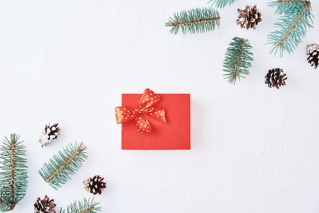 Kerstmissamenstelling met exemplaarruimte. geschenkdoos versierd met fir boomtakken en dennenappels op witte achtergrond