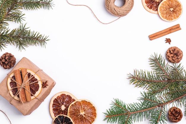 Kerstmissamenstelling met geschenkdoos van handgeschept papier, gedroogde citrusschijfjes, kaneel, dennenappels