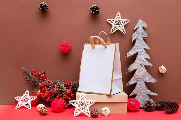 Kerstmissamenstelling met geschenken en een houten kerstboom, dennenappels en sterren