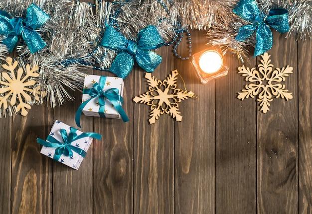 Kerstmissamenstelling met giften, kaars en decoratieve sneeuwvlokken op houten achtergrond