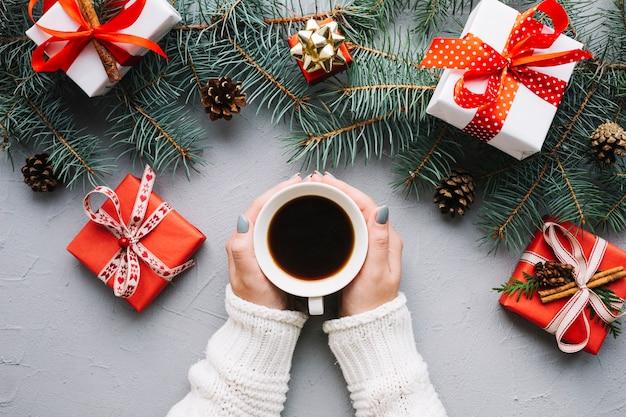 Kerstmissamenstelling met handen die koffie en cadeaus houden