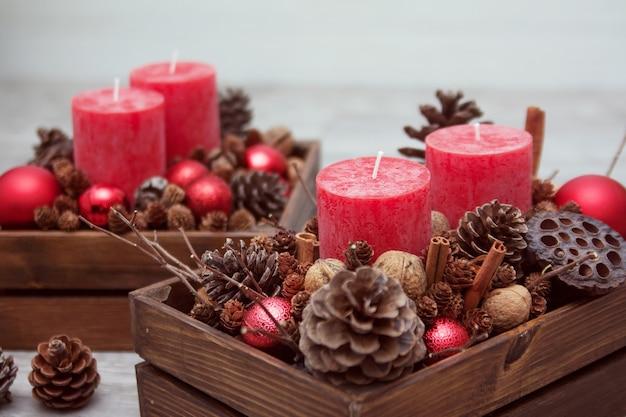 Kerstmissamenstelling met kaarsen, kegels en noten in een houten doos