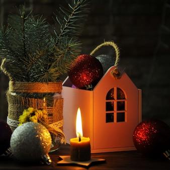 Kerstmissamenstelling met kerstmisspeelgoed, een kaars en een huisje