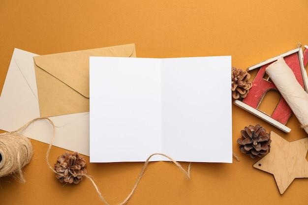 Kerstmissamenstelling met lege kaart en enveloppen op kleurenachtergrond