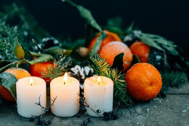 Kerstmissamenstelling met mandarijnen, denneappels, okkernoten en kaarsen op houten achtergrond.