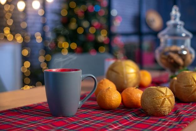 Kerstmissamenstelling met mandarijnen en een kop thee. nieuwjaar huis kamer met boom en feestelijke bokeh verlichting.