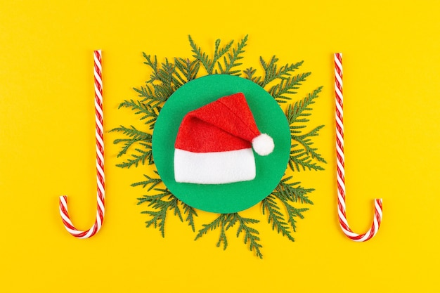 Kerstmissamenstelling met naaldboomtakken op geel document achtergrond. rond frame van kerstboomtakken en decoraties met ruimte voor tekst. bovenaanzicht. nieuwjaar concept