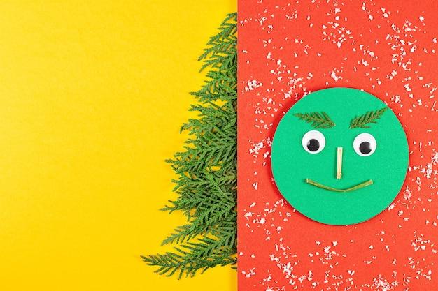 Kerstmissamenstelling met naaldboomtakken op geel papier