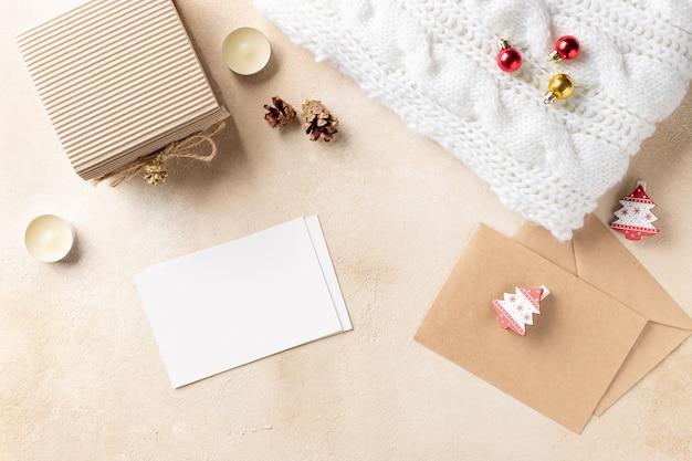 Kerstmissamenstelling met papieren kaart, geschenkdoos, gebreide plaid en kerstversiering