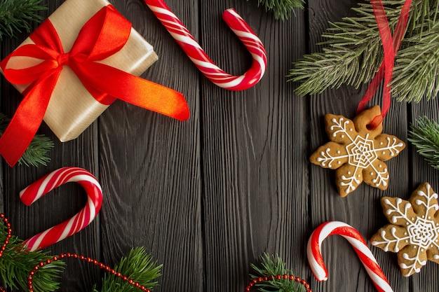 Kerstmissamenstelling met peperkoek en gift op zwarte houten.