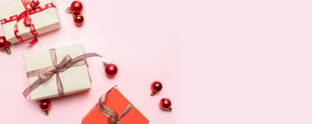 Kerstmissamenstelling met rode huidige doos, linten, rode grote en kleine ballen, vakantiedecoratie op roze. plat lag, bovenaanzicht, copyspace