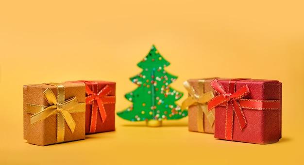 Kerstmissamenstelling met selectieve aandacht. geschenkdozen en kerstboom op een gele achtergrond met kopie ruimte.