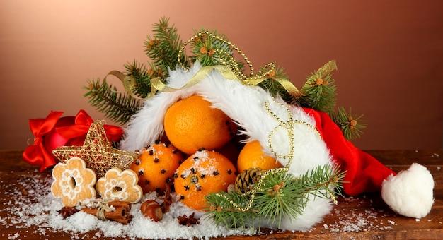 Kerstmissamenstelling met sinaasappelen en spar in kerstmanhoed