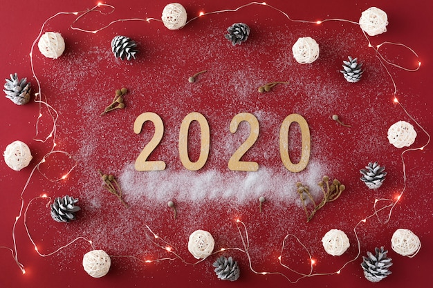 Kerstmissamenstelling met slinger, sparappel, 2020 en witte ballen op rood