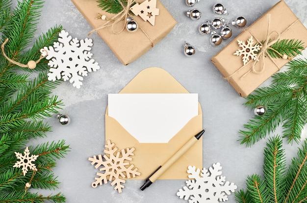 Kerstmissamenstelling met sparrentakken, decoraties, geschenkdozen en envelop met lege kaart en pen