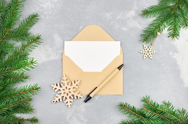 Kerstmissamenstelling met sparrentakken en envelop met lege kaart en pen