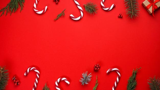 Kerstmissamenstelling met suikergoed en kerstdecoratie op rood, copyspace. plat leggen.