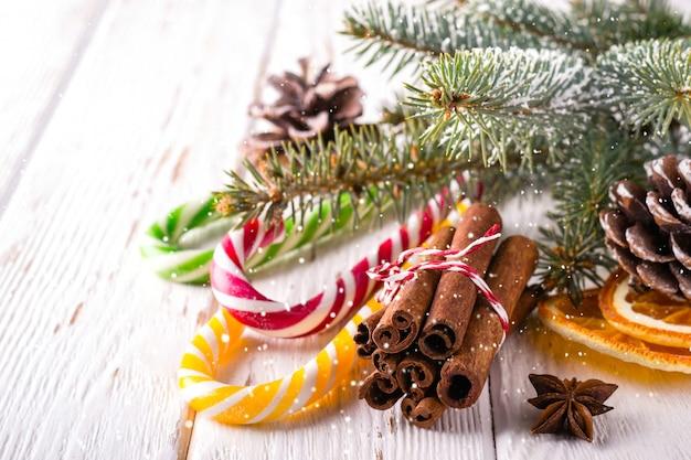 Kerstmissamenstelling met suikergoedriet en pijpjes kaneel op witte houten achtergrond