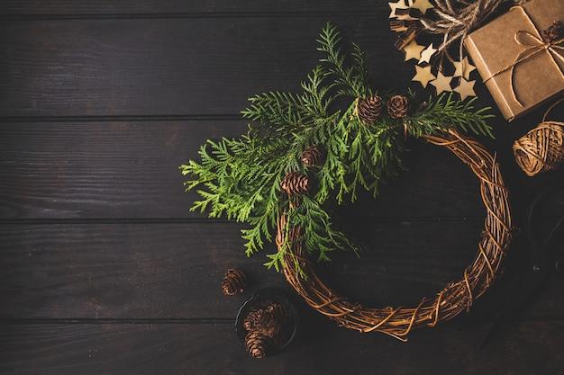 Kerstmissamenstelling op donkere achtergrond. kerstmiskroon, giftdoos en de achtergrond van de kerstmisdecoratie.