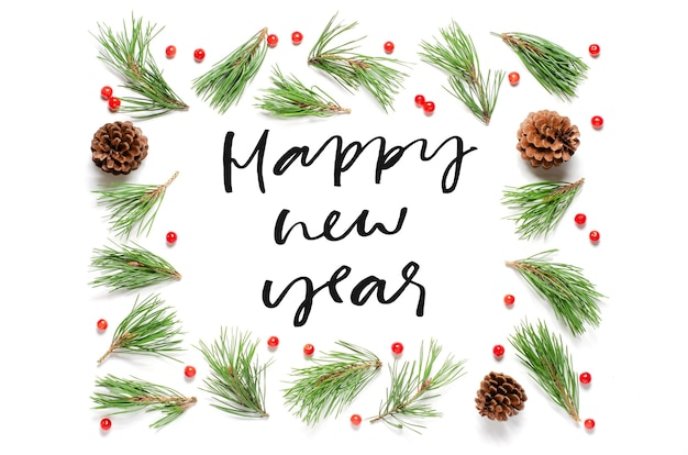 Kerstmissamenstelling op een witte achtergrond. pijnboomtakken en kegels. gelukkig nieuwjaar handgeschreven inscriptie. Premium Foto