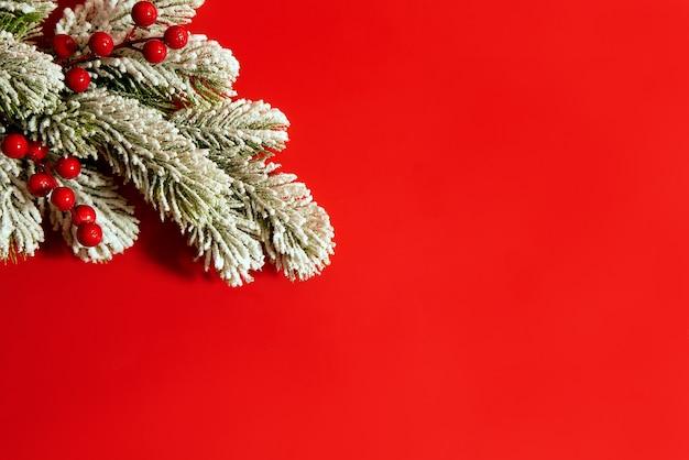 Kerstmissamenstelling op rode die achtergrond van sneeuwboom en rode bessen wordt gemaakt. kerst concept, plat lag, bovenaanzicht, kopie ruimte.