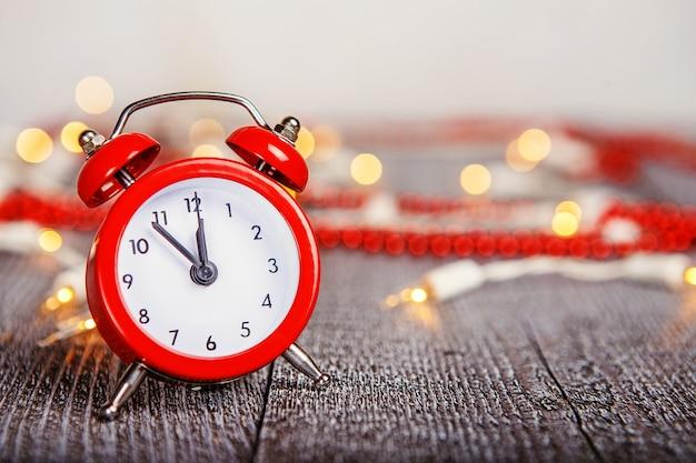 Kerstmissamenstelling - rode wekker op een geweven houten raad met lichten en parels bokeh