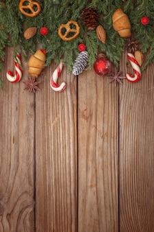 Kerstmissamenstelling van boomtakken, suikergoed en decoratie op houten achtergrond. bovenaanzicht kopieer ruimte.