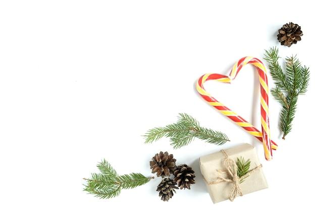 Kerstmissamenstelling van dennenappels, dennentakken, kerststokken, geschenkdoos. bovenaanzicht, plat gelegd