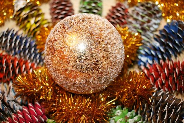 Kerstmissamenstelling van geschilderde sparappel, klatergoud en een glanzende gouden bol.