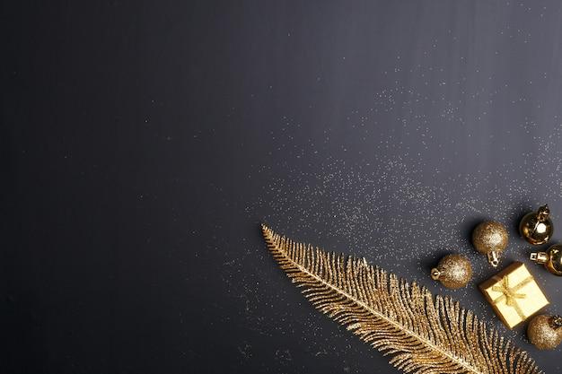 Kerstmissamenstelling van gouden kerstmisspeelgoed en decoratieelementen op een zwarte achtergrond.