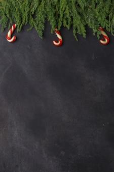 Kerstmissamenstelling van naaldtakken, decoratie en snoepjes op donkere achtergrond. plat leggen. bovenaanzicht natuur nieuwjaar concept. kopieer ruimte.