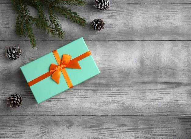 Kerstmissamenstelling van nette takken, giftdoos, sparappel op rustieke grijze houten achtergrond.