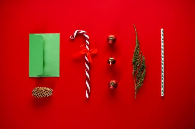 Kerstmissamenstelling van snoep en kerstversiering op rood met een groene envelop. plat leggen.