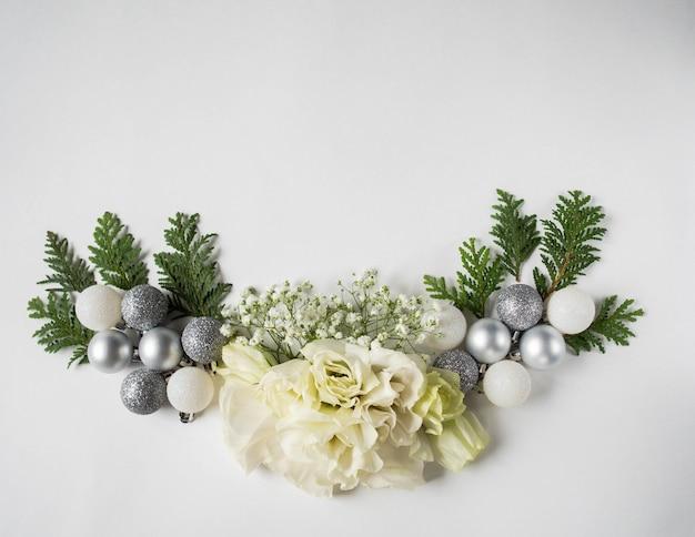 Kerstmissamenstelling van verse witte bloemen, zilveren kerstballen en thuja