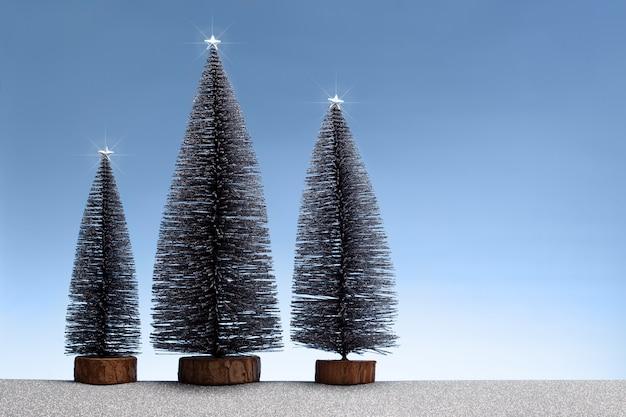 Kerstmisscène met miniatuursparren en sparkly zilveren grond en blauwe hemel. kopieer ruimte