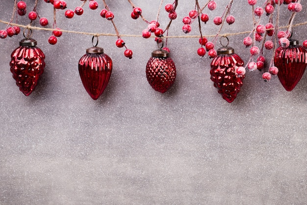Kerstmisslinger met rode bal en grijze achtergrond.