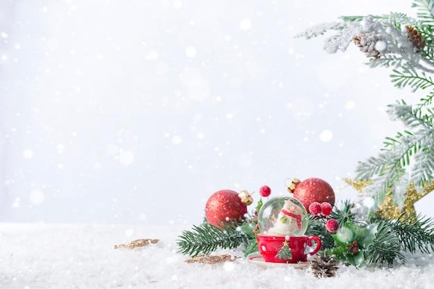 Kerstmissneeuwbol met pijnboomtakken en feestelijke decoraties op sneeuwtafel. kerstmis of nieuwjaar concept