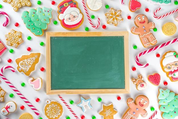 Kerstmissnoepjes en schoolbord. geassorteerde feestelijke kerstsnoepjes, traditioneel snoep en koekje. flatlay met snoepgoed, peperkoek, snoep, eenvoudig bovenaanzicht van het patroon