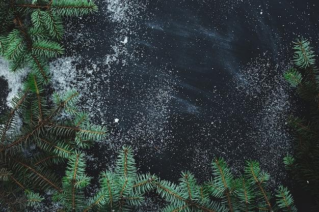 Kerstmisspar op het donkere oppervlak met sneeuw