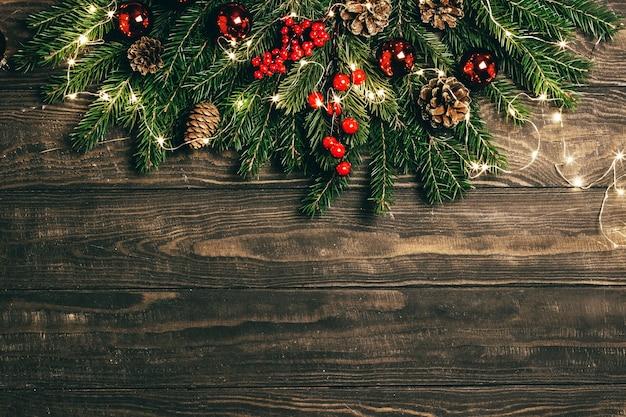Kerstmisspar takken, winter bessen, dennenappels en garland op bruine houten achtergrond