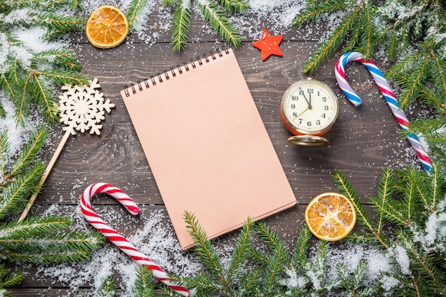 Kerstmissparren in sneeuw met kegels, snoepriet, uitstekende klok