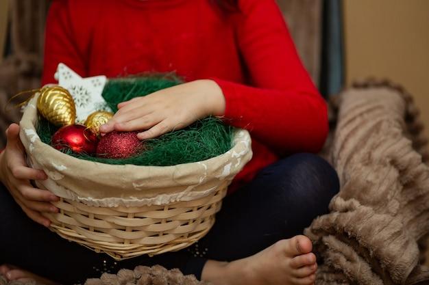 Kerstmisspeelgoed in een mand in handen van de vrouw
