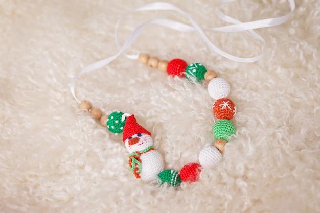 Kerstmisspeelgoed - kralen en een sneeuwpop gemaakt van katoen op een witte vachtachtergrond. kersttijd. nieuwjaar en wintervakantie