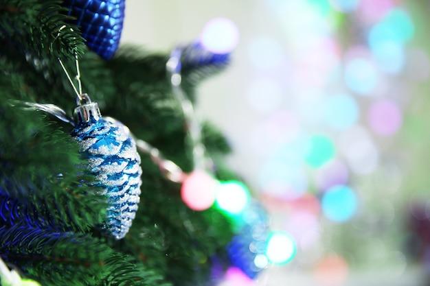 Kerstmisspeelgoed op een dennenboom over onscherpe achtergrond