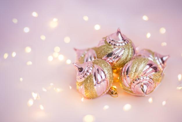 Kerstmisspeelgoed op een lichtrose oppervlakte met lichten