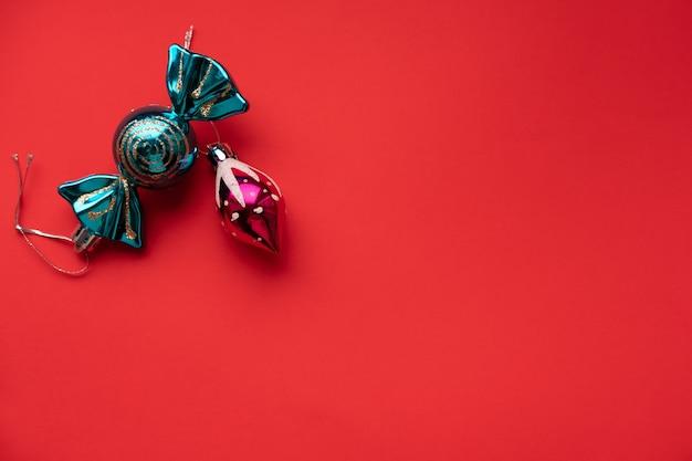 Kerstmisspeelgoed op rood met plaats voor tekstconcept kerstmis en nieuwjaar